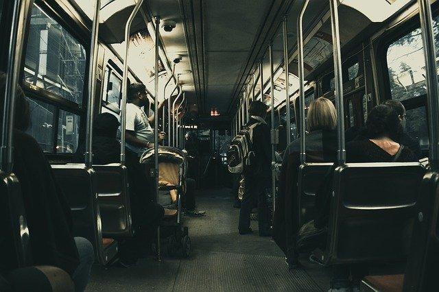 autobus zevnitř, lidé sedící a stojící, vše je tmavé
