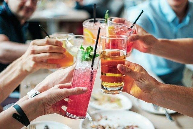 lidé si ťukají sklenicemi naplněnými různými drinky i barevnými